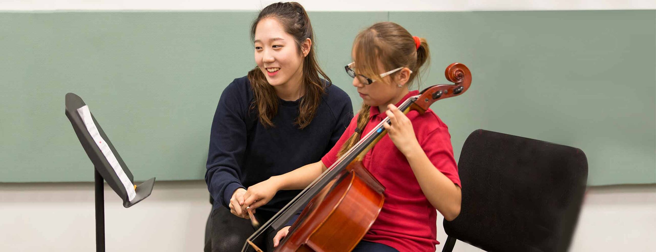 Conservatory student teaching a Jumpstart cello student