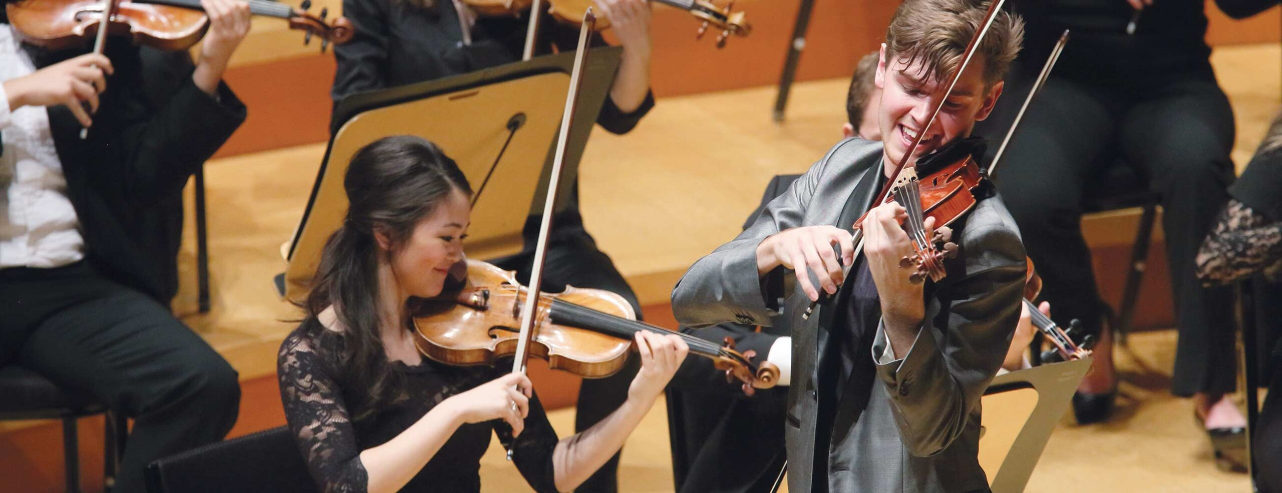 Violinists Simone Porter and Blake Pouliot performing on stage with orchestra