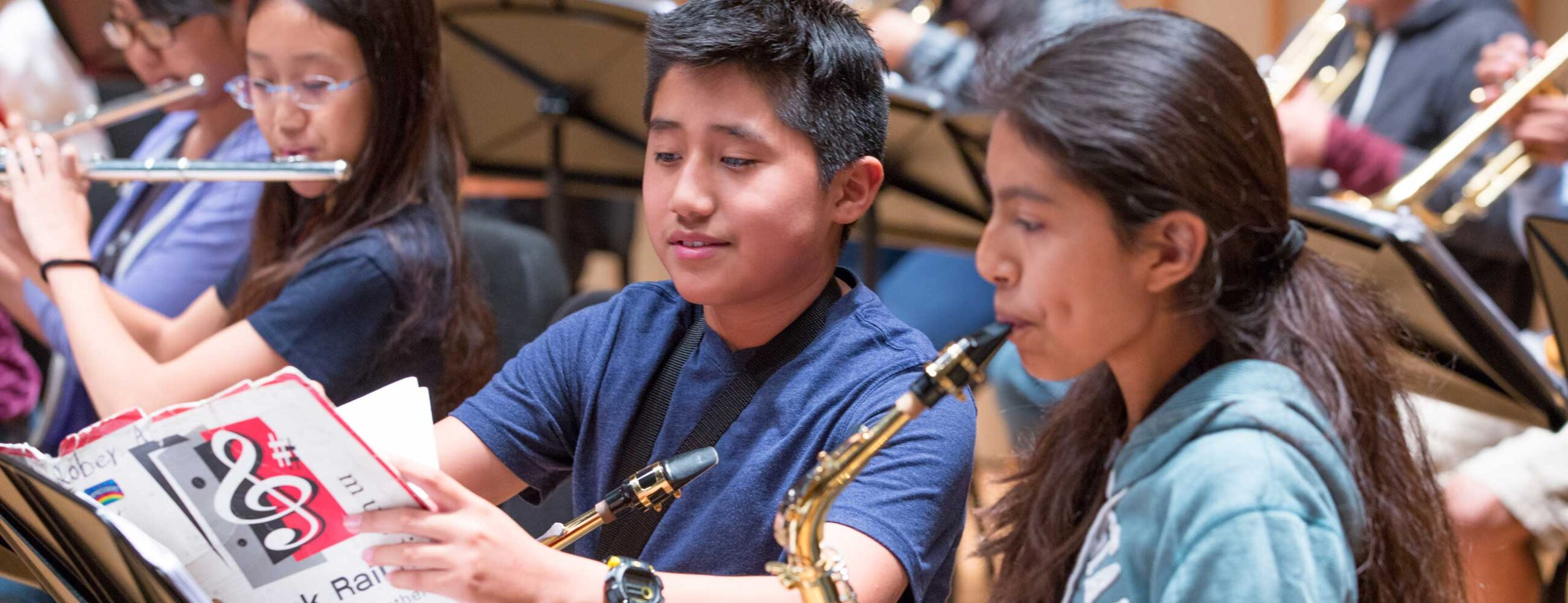 Two young saxophone students looking at music in rehearsal