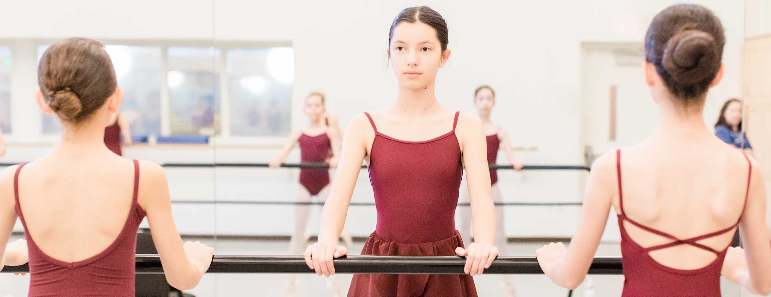 Ballet students standing at barre