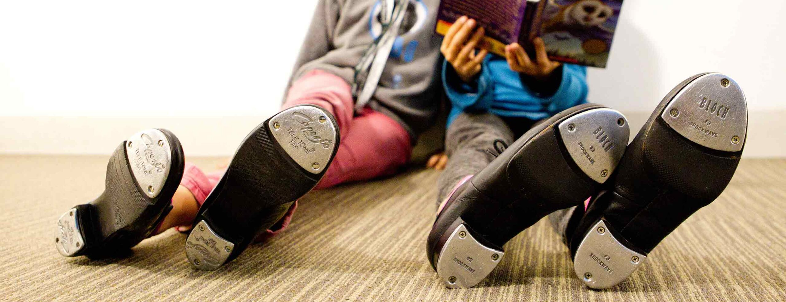 Kids sitting on floor with tap shoes visible