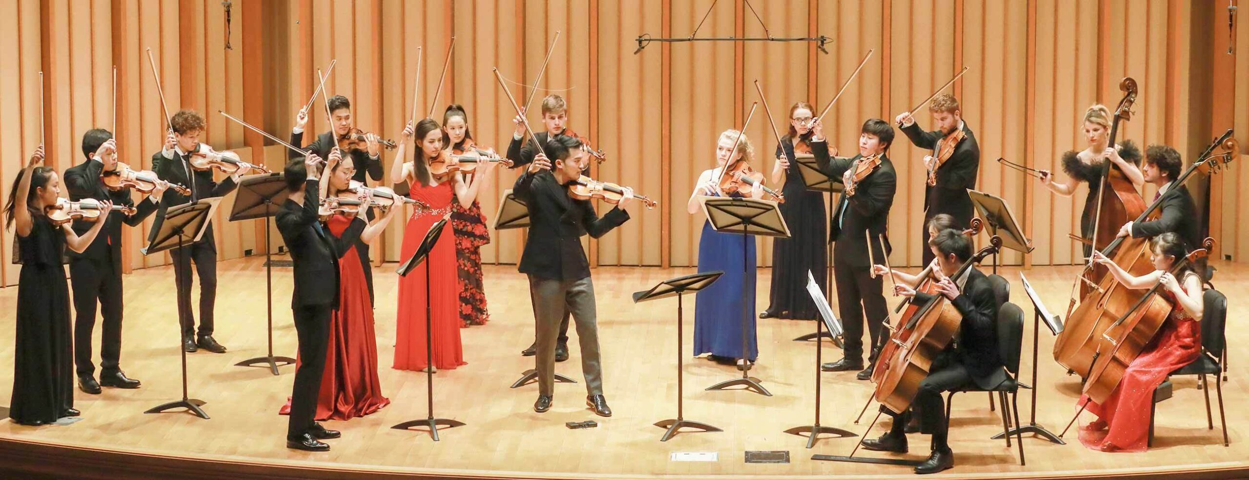 Small chamber orchestra standing on stage with soloist Ray Chen